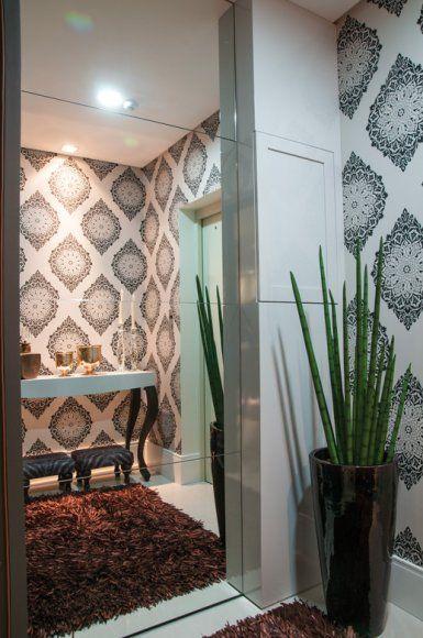 No hall de entrada do apartamento, o papel de parede é o destaque, valorizado pela instalação de um painel de espelhos.
