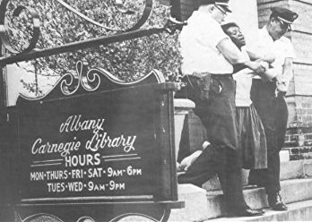 Woman arrested for trying to read a book in a segregated library in  Albany, GA. 1962.