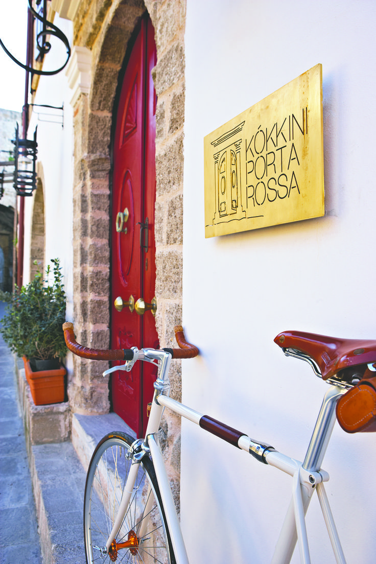 """EXCLUSIVE SUITES BOUTIQUE HOTEL. MEDIEVAL TOWN, RHODES, GREECE. - Our red front door. Older than one hundred years, made of """"katrani"""", a now extinct kind of cypress wood. It was mainly used for boat keels and roof beams. The brass handles and knocker were found in a scrap yard. The iron latch was hand-forged in Italy. The white marble step was part of the staircase of a 19 cent. house in Athens. The bike can be seen at http://metronariston-share.blogspot.gr/   .-   kokkiniporta.com"""