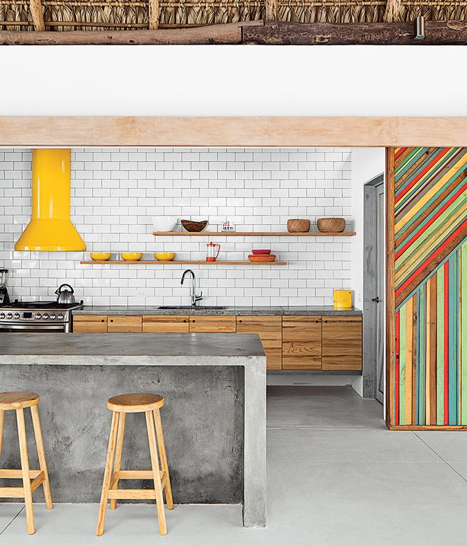 In the kitchen, rough-hewn materials like a eucalyptus-log-and-thatch roof offset the monolithic concrete island and glossy subway tile b...