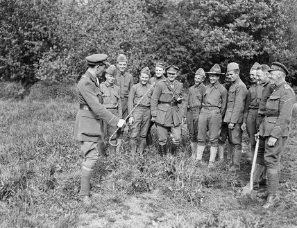 Men of the American 77th Division receiving instruction in camouflage and sniping from the British at Moulle, 22 May 1918. A camouflaged sni...
