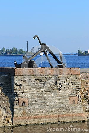 Admiralty anchor and Hall anchor stand on the stone quay in Kronshtadt on a sunny day. Saint-Petersburg, Russia
