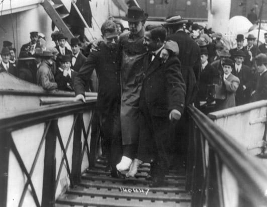 Harold Bride, the Titanic's junior wireless operator, sent distress signals as the ship took on water. He survived by clinging to an overturned collapsible lifeboat, although his feet were frostbitten. Here he is carried up a gangway after the rescue ship, the RMS Carpathia, arrived in New York. (Universal History Archive/Getty Images)