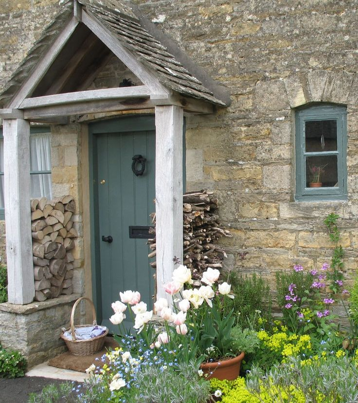 Old English country cottage showing door and porch. Love the blue used on the door and window frame.