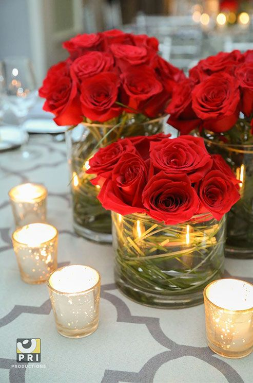 Modern arrangements of red roses add a burst of color to this chic table setting. Wedding Centerpiece Ideas