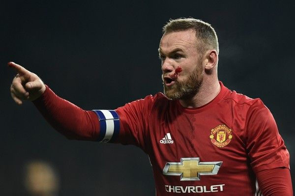 Blood covers the cheek of Manchester United's English striker Wayne Rooney as he remonstrates with referee Mike Jones during the EFL (English Football League) Cup quarter-final football match between Manchester United and West Ham United at Old Trafford in Manchester, north west England, on November 30, 2016. / AFP / Oli SCARFF / RESTRICTED TO EDITORIAL USE. No use with unauthorized audio, video, data, fixture lists, club/league logos or 'live' services. Online in-match use limited to 75…