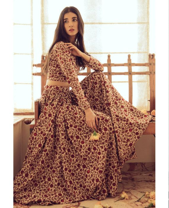 This cream, ochre and red floral lehenga set contains a lehenga skirt and blouse. The skirt and blouse are crafted from pure cotton that has been