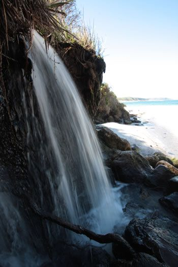 Waterfall Beach is a few kilometers east of Greens Pool along the bitumen road. The carpark is close to the carpark for Madfish Bay. See the Map below.    We visited Waterfall beach in winter when the waterfall coursed across the heathland and poured out over weathered rocks and down to the beach.    The beach is somewhat sheltered with BEAUTIFUL turquoise waters. The waterfall is on the far side of the beach, to the left from the carpark.