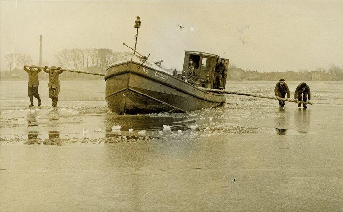 Het motorschip Courier van kapitein H. Ferbeen bij de Koninklijke Nederlandsche Maatschappij-fabriek te Oudega (Wymbritseradeel) uit het ijs van de Brekken gewrikt. ca.1955