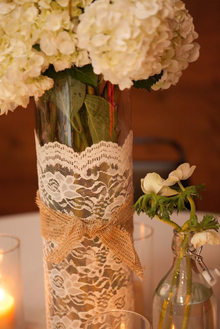A fast and low cost centerpiece- take dollar store vases, trim with lace and ribbon, then add flowers. #lovelyinlace