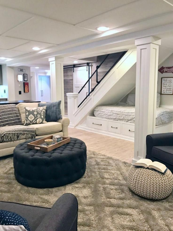A HGTV fixer Upper basement remodel with shiplap wood walls, sliding barn doors, and industrial chic accents. A cozy reading and lounging nook was created under the stairs with extra storage. #Rugs