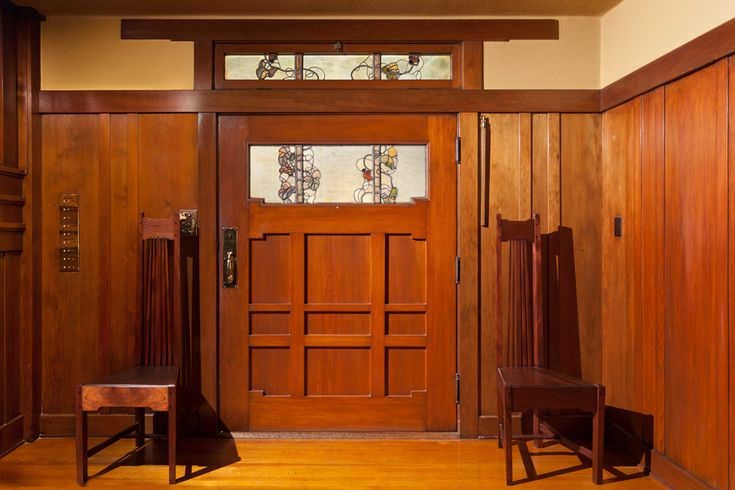 Extra wide front door. Wainscoting in the entry is shown. This home, like several other homes designed by the Greene brothers, included custom furniture. The Greenes collaborated with craftsmen Peter and John Hall, who produced the decorative arts and furniture that the brothers designed for the homes, according to Edward Bosley, director of the Gamble House in Pasadena.