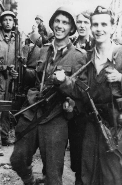 """Members of Battalion """"Kiliński"""" after securing the PAST-a building on 20 August 1944. From left to right: Zbigniew Maliński """"Sławicz"""", Edward Mortko """"Tumry"""" with machine gun, Kazimierz Zagórski """"Barbara"""" and Bernard Zieliński """"Połabski""""."""