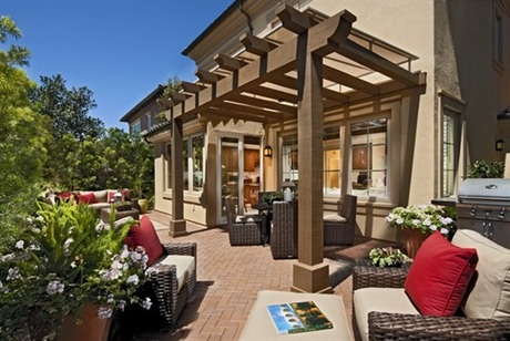 A timber trellis and sun screen define this brick patio. Red pillows provide contrast, as white flowers spill from an over-sized planter. Residence 1. The Siena new home community by Irvine Pacific. Orange County, CA.