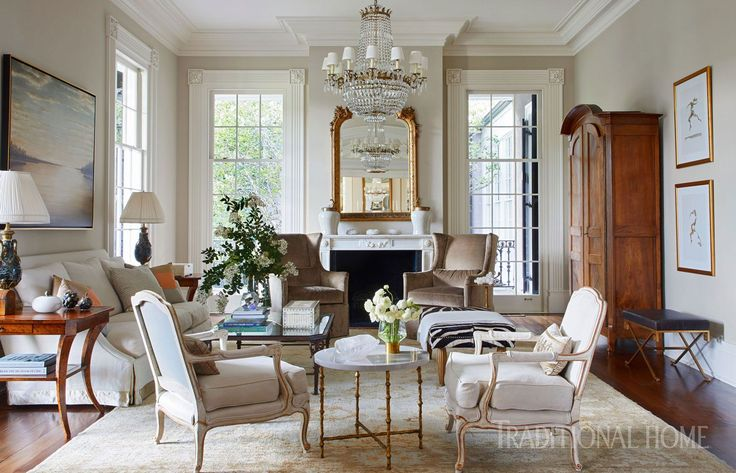 Pairs of chairs in the living room offer contrasting forms. Tall wing chairs by Chaddock in front of the fireplace are covered in taupe velvet and exhibit an at-full-attention posture. Across the room, bergères wear white linen and are highlighted with gold around the curvy edges of their frames. An old armoire offsets the new sofa from Lee Industries. - Photo: Jean Allsopp / Design: Lisa Palmer #TraditionalDecor