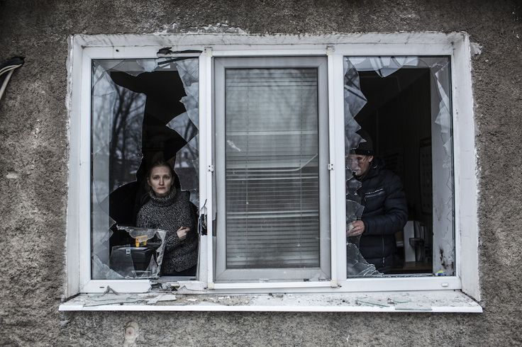 A woman looks through a broken window after it was hit by Ukrainian Artillery in the center of Donetsk [980x653] Photo by Manu Brabo