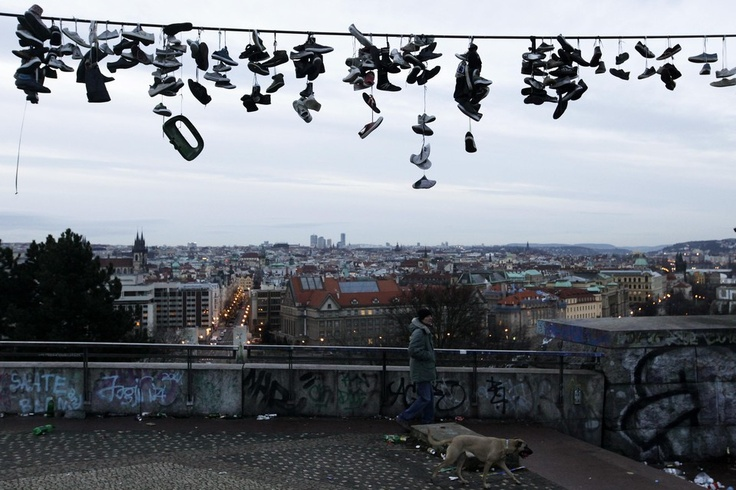 A man walked his dog in Prague's Letna park early Wednesday. Teenagers who skateboard at the park throw their damaged and unwanted shoes over the wire for fun at the site, once the location of a monument to former Soviet leader Josef Stalin. (Petr Josek/Reuters)