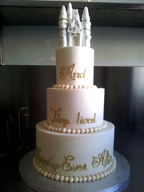3-tier Wicked Chocolate wedding cake iced in smooth white chocolate ganache, decorated with 3D Fairytale Castle on top tier, with piped gold scripty wording & edible pearl bollas at bases by Charly's Bakery, via Flickr