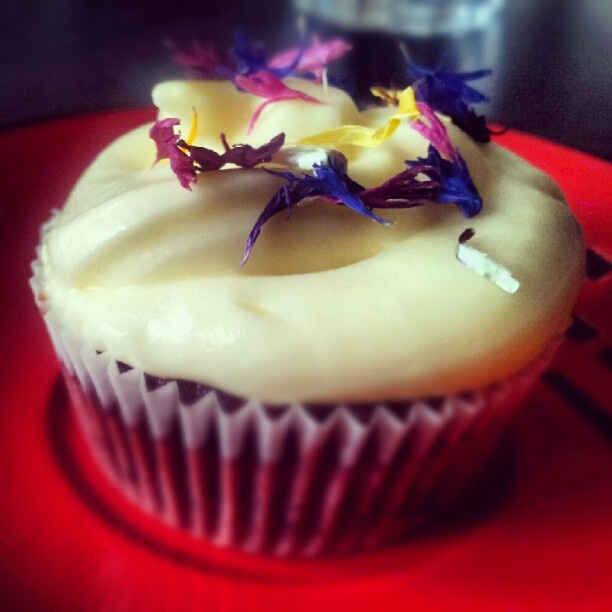 Red velvet cupcake with white chocolate buttercream frosting, garnished with dried cornflower and marigold