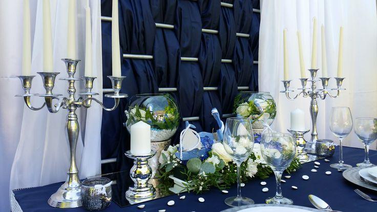 Az ezüst és üveg  kiegészítők csillogása, tovább emeli a tengerészes esküvő fényét