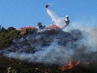 A helicopter dumps water on the lighthouse at Palm Beach NSW. Picture: Courtesy Instagram