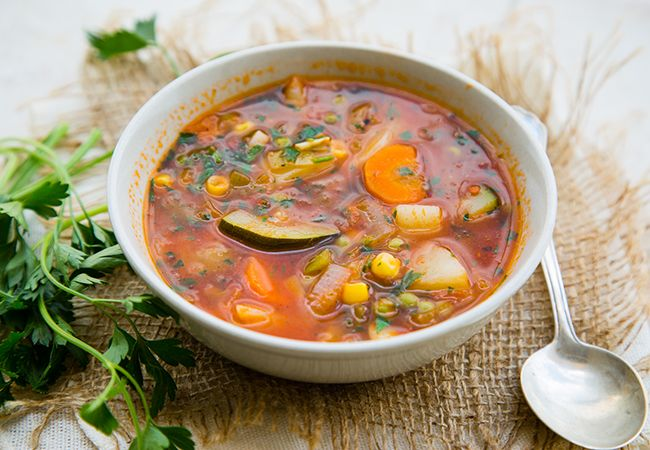 Vegetable soup for earth day, tomato broth loaded with fresh veggies