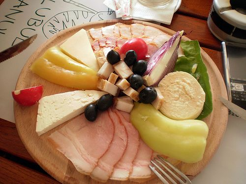 traditional Romanian food plate - ham, bacon, cheese, olives, paprica, radish - at Romanian Paesant Museum in Bucharest