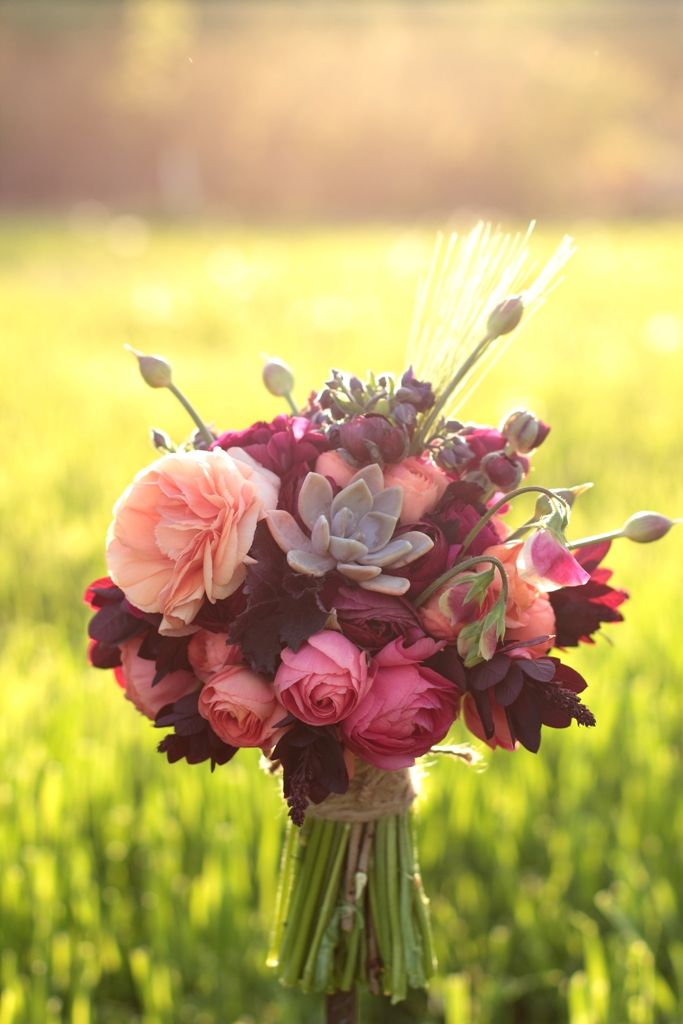 Ranunculus and Anemones and succulents in a burgundy, peach, pink and green bridal or bridesmaid bouquet