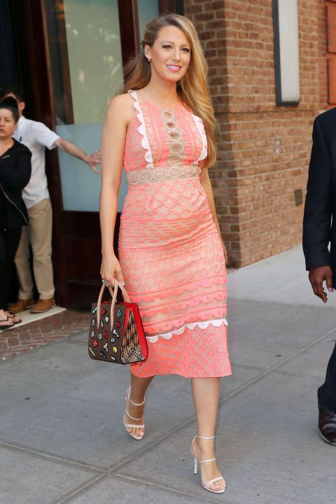 The actress steps out for a Cafe Society press junket in a sheer and peachy pink midi dress, a sticker-patterned handbag and white heeled sandals.