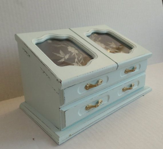 Vintage wood jewelry box painted mint and distressed. This jewelry box has two lift up glass doors with hummingbird design, a ring pillow, four