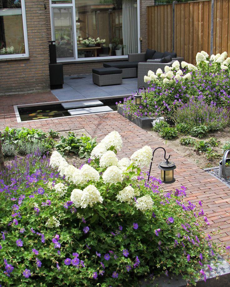 Tijd om te genieten! De verschillende zitjes zijn verbonden door het kleurgebruik in de beplanting. De loop van het pad en de zwevende stapstenen in de vijver zijn bepalende elementen in deze tuin.