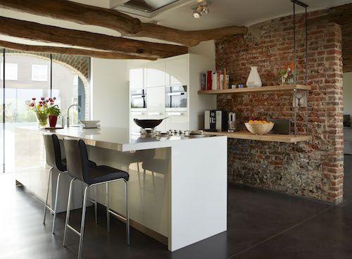 In deze landelijke keuken is er gekozen voor hoogglans wit, een bakstenen muur en houten balken. Keukendealer: www.haroldlenssenkeukens.nl