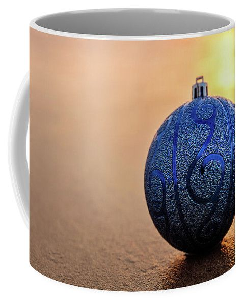 Coffee Mug featuring the photograph Blue At Sunset by Evgeniya Lystsova. Closeup of blue Christmas ball at the beach at sunset time, winter holiday concept. Christmas is the time of giving and receiving gifts. Have fun of finding something special for your family, husband, wife, kids and friends! More options of Art Products (Prints, Home Decor, Lifestyle) you can find in my gallery. #EvgeniyaLystsovaFineArtPhotography #Christmas #Gift #Season #Mugs #HomeDecor