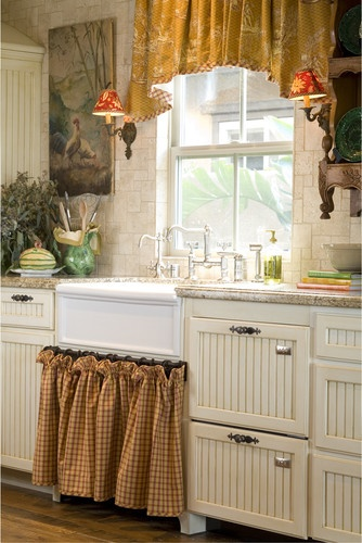 Inviting cottage kitchen  Love the cabinetry, counter top, golden arched valance above the farmhouse sink, and the knick-knack shelf.