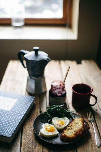 ハートに焼いた目玉焼きがとっても素敵な朝食風景です。 もちろん、パンとコーヒーも忘れていませんよ。  しっかりトーストしたアツアツのパンには、ジャムがそっと甘みと酸味で味を引き立ててくれます。  ちょっとのんびり起きた休日には、こんな朝食も素敵ですね。
