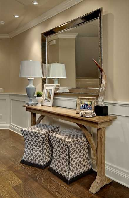 wooden console table with table lamp and large wall mirror