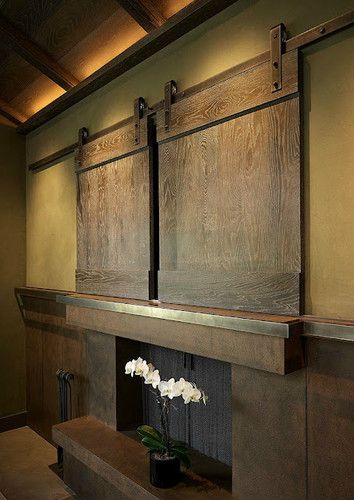 OMG I love this! I've been wanting a creative way to hide the TV so it's not the center of focus in the living room. Hiding a flat screen TV -- sliding barn door hardware.