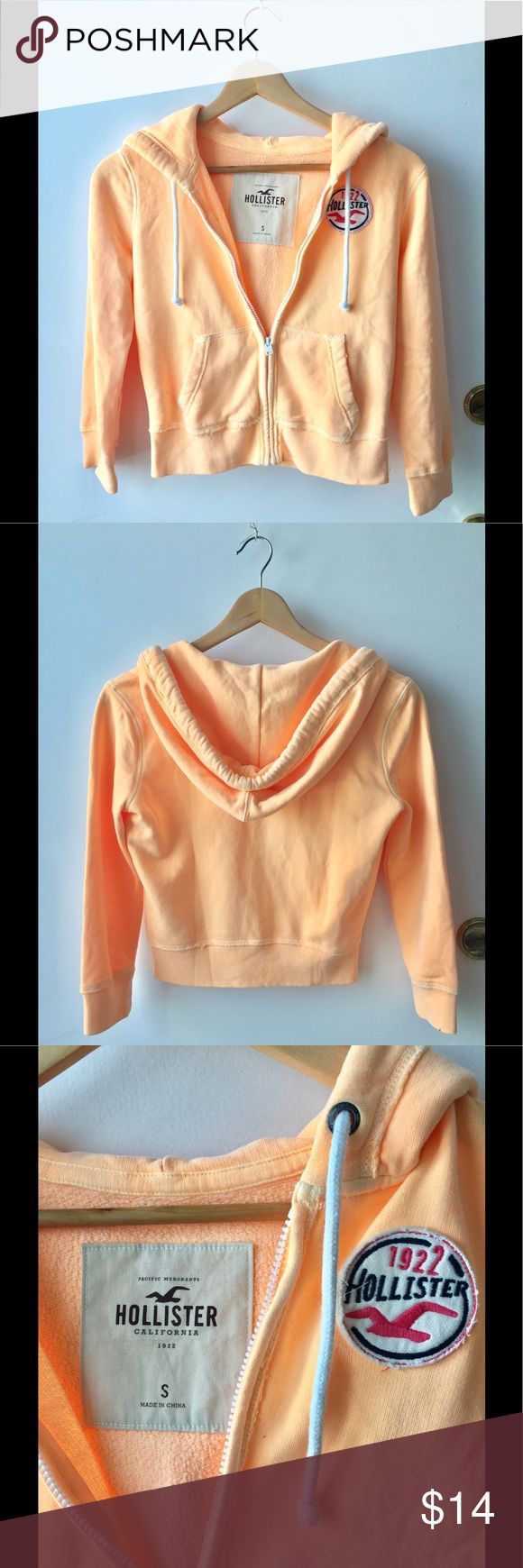 Hollister Orange Zip Up Cute Hollister orange creamsicle color zip up hoodie. Quarter sleeves. Hollister logo on front. Has drawstring detailing around hood. Perfect for summer nights ✨  Size: S  Condition:  Pre-owned. No rips or stains. In excellent condition! Hollister Sweaters Crew & Scoop Necks