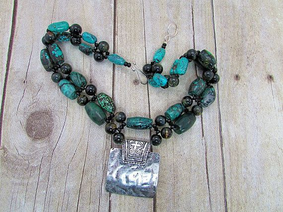 Turquoise and Tiger Eye Necklace with Tribal Pendant. A square tribal pendant was hung with turquoise and tiger eye beads that I wove together with black Swarovski crystals and glass Czech beads to create this rustic and earthy necklace. I finished it off with a silver metal hook clasp.