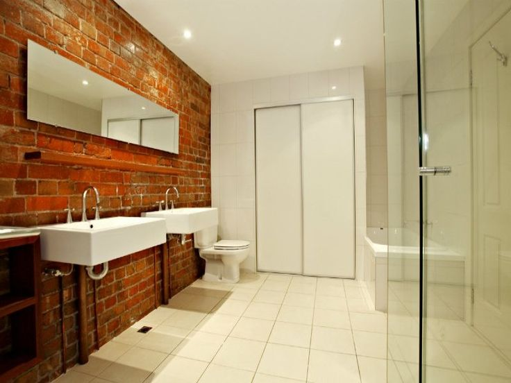 Exposed red brick feature wall for the modern bathroom for Feature wall bathroom ideas