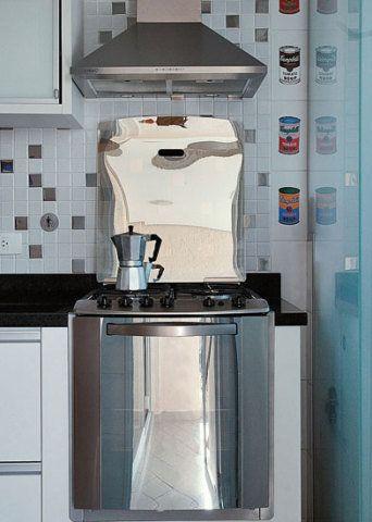 Ao lado do fogão (Electrolux), uma porta de vidro jateado esconde a lavander...