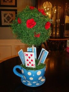 Alice in Wonderland centerpiece idea: take a tea cup shaped flower planter and add a (fake) rose bush and playing cards