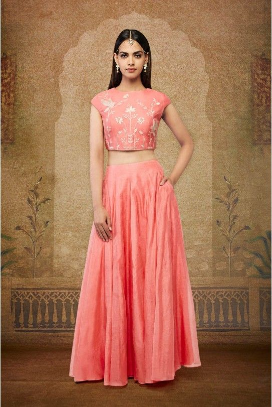 A peach Maheshwari crop top with delicate thread and zari embroidery on front and back in motifs of chirping birds and blooming flowers inspired by a magical forest, paired with a matching flared skirt.