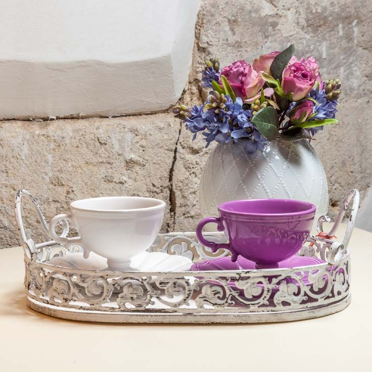 A bunch of flowers between you and me. A lilac cup in front of a shell cup. Both of us sitting on an antique tray