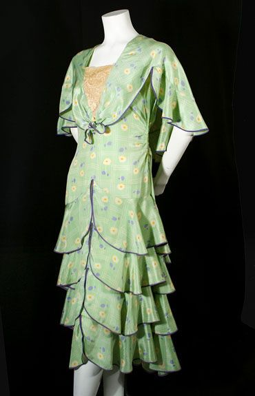 Printed silk day dress, late 1920s. Made from pale green silk crepe de chine  printed with plaid lines and flowers, the sleeveless torso is straight to the hipline, where it breaks to overlapping rows of bias-cut ruffles. The large cape collar (tying in front) forms faux sleeves.