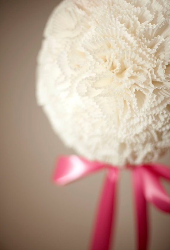 """Over 250 white linen colored cupcake liners have been attached, one by one to a handmade paper mache form. The completed kissing ball measures to a diameter of 9"""" and the height of 20"""" - 36"""" (depending on how long you make the bow it is hanging from on top). Hanging from a wonderful shade of pink satin ribbon with a draping bow beneath, this pomander is perfect to add that final touch to almost any decor need."""