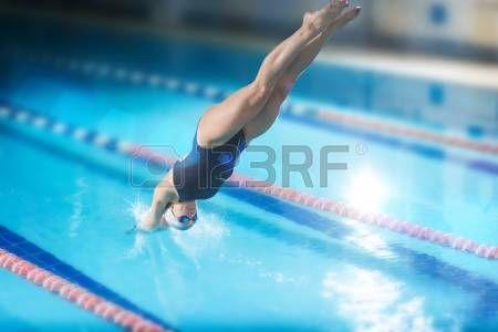 Portret van een vrouwelijke zwemmer, die springen en duiken in binnen- sport zwembad. Sportieve vrouw. photo