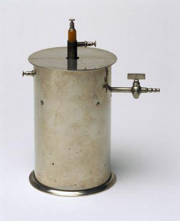 Noticia Nº34: Becquerel, Marie Curie y los minerales de uranio.   Noticias de un Espía en el Laboratorio  Camara de ionización fabricada por Pierre Curie. Electrónicamente es un condensador cilíndrico. La ionización del aire dentro del cilindro debido a la radiación hace que se produzca una pequeña corriente eléctrica, medible con un aparato sensible llamado electrómetro. Este aparato es el antecesor del famoso contador Geiger.