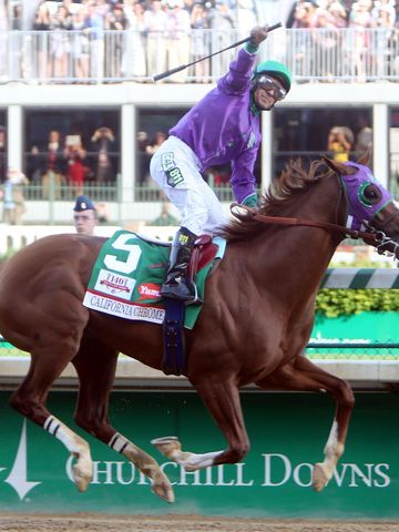 Victor Espinoza aboard California Chrome celebrates as they cross the finish line to win the 2014 Kentucky Derby at Churchill Downs.