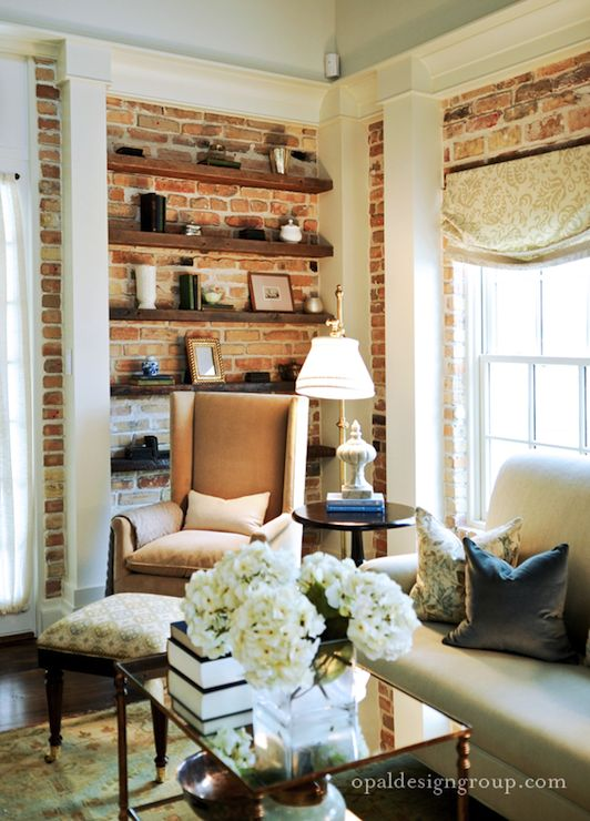 Fantastic living room with exposed brick wall, white sofa, blue velvet pillow, camel velvet wingback chair, brown floating shelves and brass tiered cocktail table.